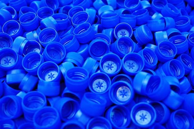 Lots of plastic blue pet bottle caps close up. Premium Photo