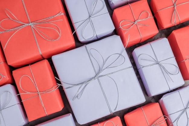 赤と薄紫色の紙の背景に包まれたたくさんのプレゼント