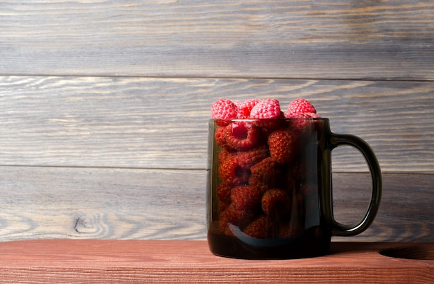 Lots of red ripe raspberries in a glass cup.