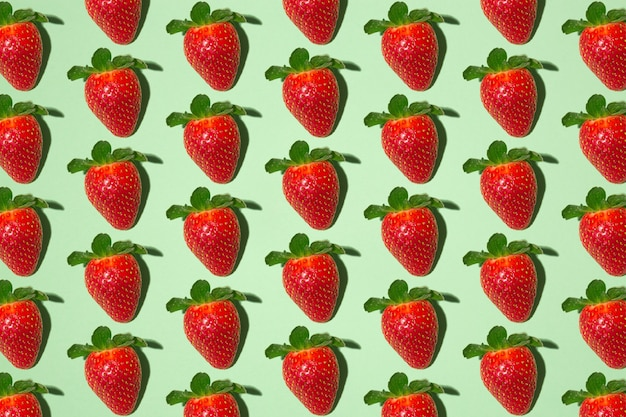 Lots of red ripe strawberries on a seamless green background.