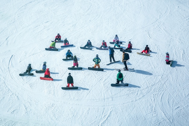 Lots of skiers and snowboarders have a rest on a slope at ski resort
