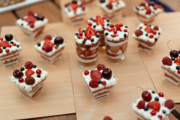 Lots of sweet desserts in cups with summer berries.