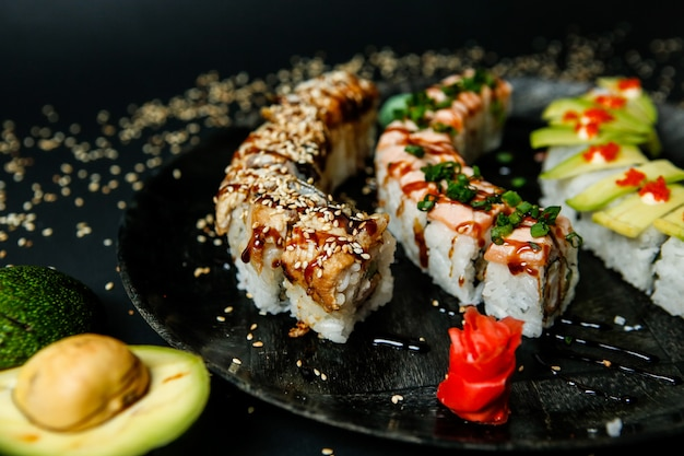 Lots of various types of sushi rolls topped with sesame seeds close-up view
