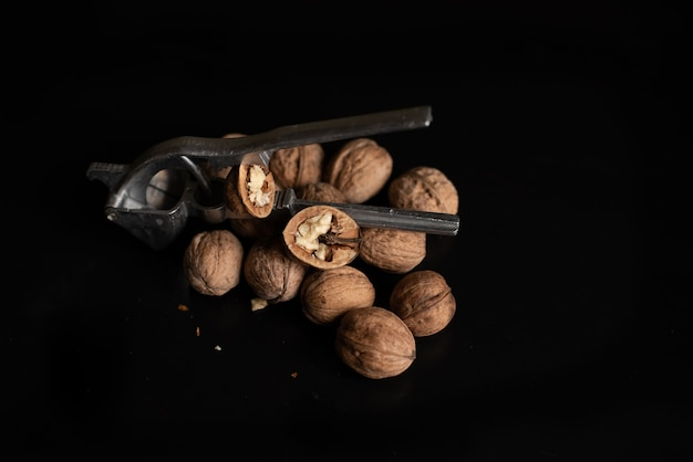 Lots of walnuts on black background and nutcracker.
