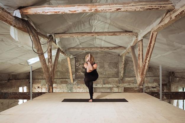 로터스. 젊은 체육 여자 버려진 된 건설 건물에 요가 연습. 정신적 및 신체적 건강 균형. 건강한 라이프 스타일, 스포츠, 활동, 체중 감소, 집중력의 개념.
