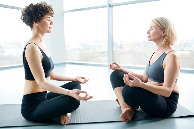 Lotus relax pose. women on mat doing yoga next to a large window