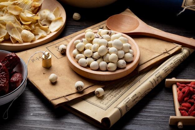 蓮はテーブルの上に古代漢方薬の本とハーブを植えます