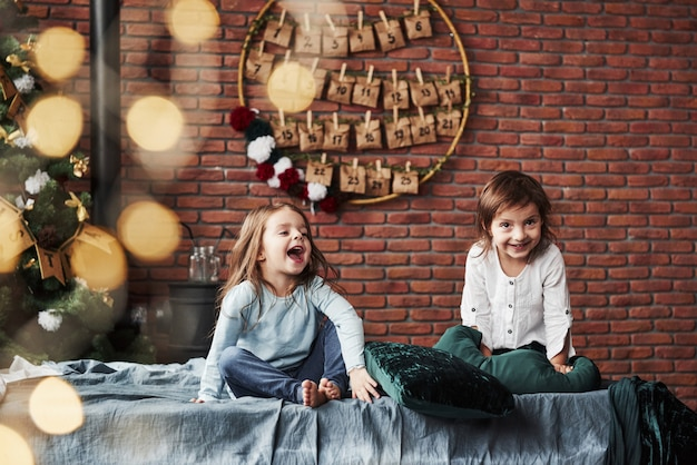 Loud laughing. little girls having fun on the bed with holiday interior at the background