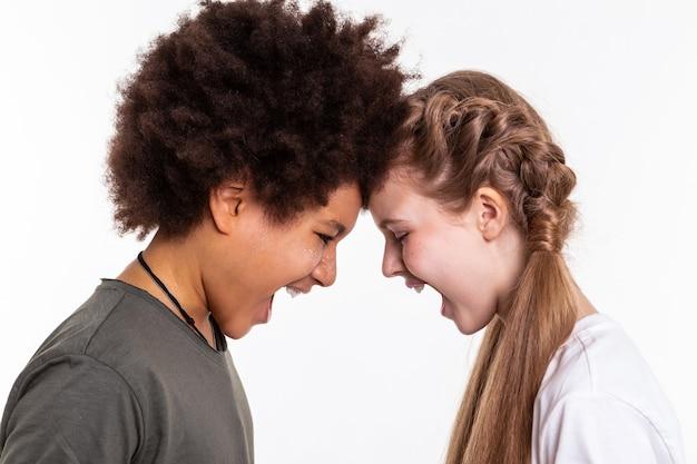 Громко кричать. агрессивно-симпатичные дети высвобождают эмоции друг на друга, соединяя лбы и открывая рты.