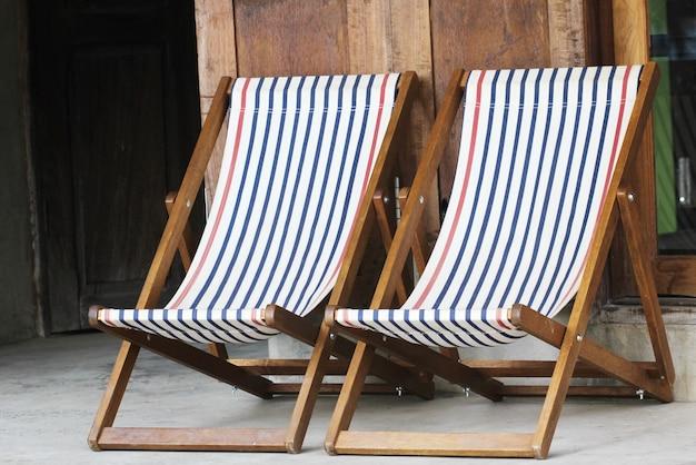 Кресло для отдыха на деревянной террасе в домашнем саду