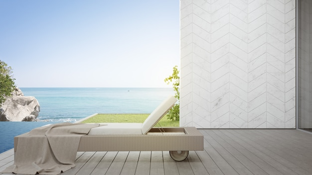 Lounge chair on terrace near swimming pool and garden in modern beach house or luxury villa