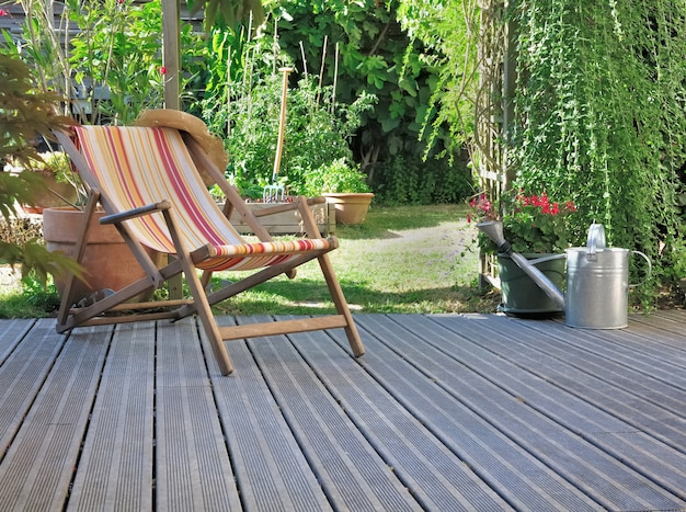 Lounge chair on wooden terrace in a home garden