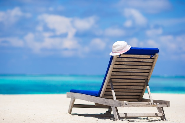 Lounge chairs with hat on tropical beach at maldives