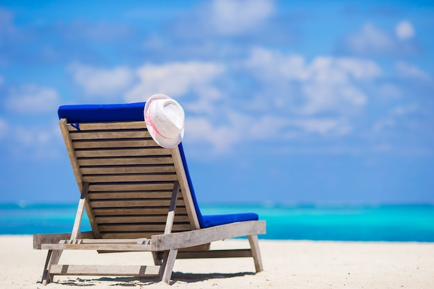 Lounge chairs with hat on tropical white beach