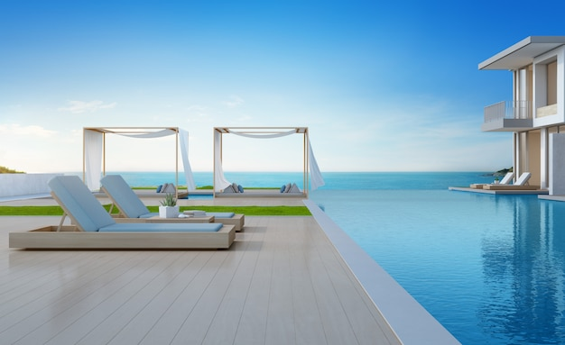 Lounge chairs on wooden floor deck at vacation home or hotel.