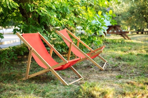 庭のサンベッドラウンジ。夏の緑の芝生に2つの木製デッキチェア。裏庭の外観。