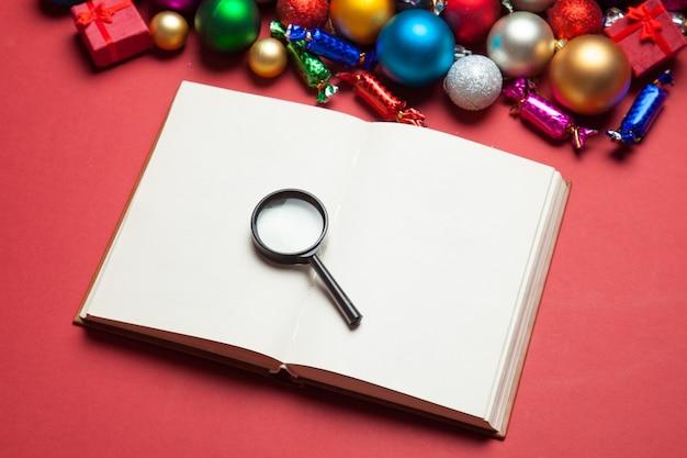 확대경 및 크리스마스 장난감 근처 책입니다.