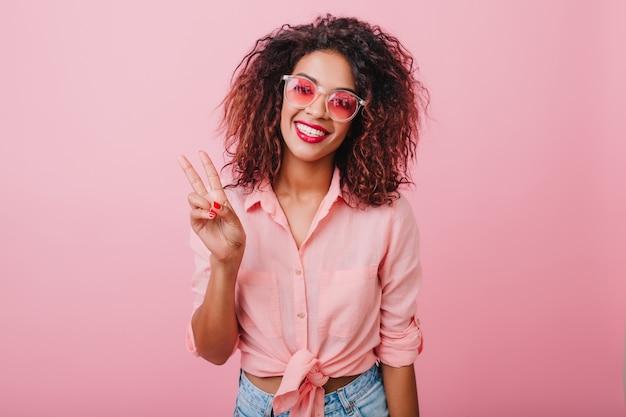 喜んでポーズをとるかわいいサングラスで愛らしいアフリカの女の子。カラフルな壁の近くに立っているヴィンテージの衣装で魅力的な巻き毛の女性。