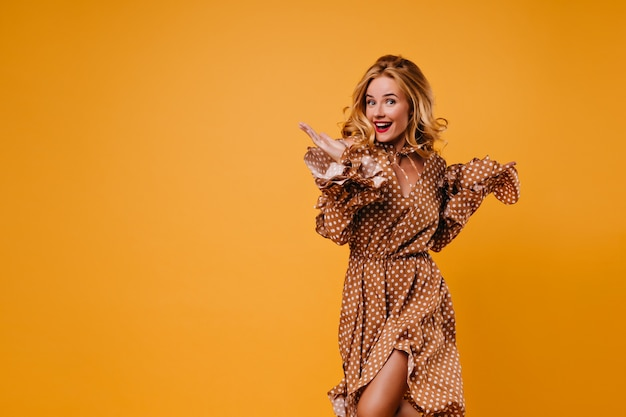 Lovable blonde girl posing with surprised smile. indoor photo of amazing european woman dancing on yellow wall.