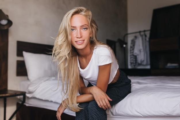 ベッドに座っている青い目をした愛らしいブロンドの女性。彼女のアパートで朝を過ごす白いtシャツを着た気さくな女性。