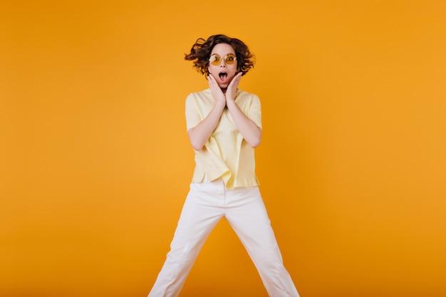 사랑스러운 갈색 머리 소녀는 충격을받은 얼굴 표정으로 점프하는 주황색 선글라스를 착용합니다. 특대 노란색 티셔츠에 우아한 백인 여자의 사진.