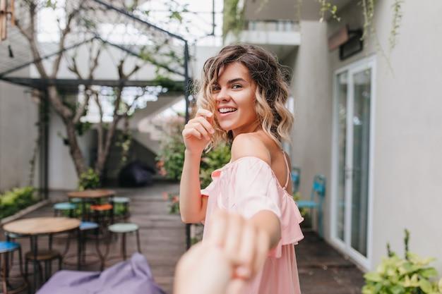 주말 아침 거리 카페에서 즐기는 트렌디 한 핑크 복장에 사랑스러운 백인 소녀. 휴가에 행복을 표현하는 곱슬 유럽 아가씨의 야외 촬영.