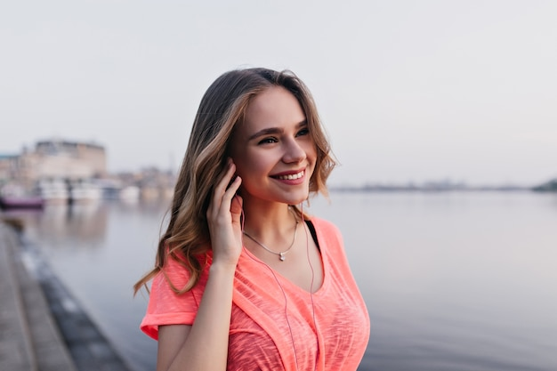 Lovable caucasian girl listening music with happy face expression while walking near river. outdoor portrait of amazing woman spending time beside lake.