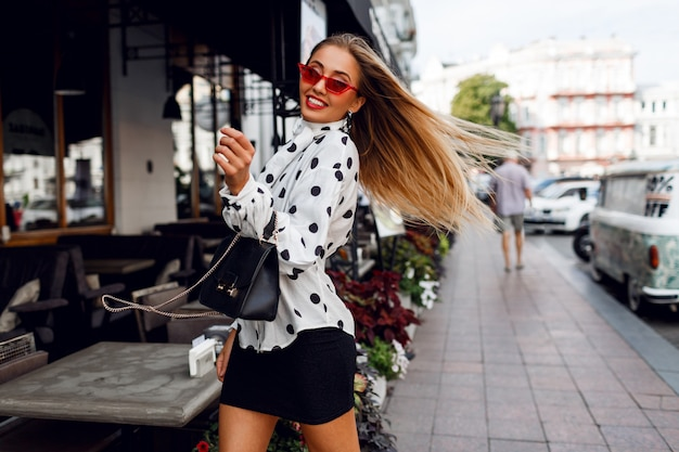 Lovable confident blond woman with long hairstyle posing on the street over modern cafe