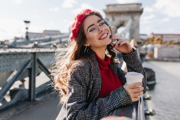 興奮して橋の上に立って、コーヒーを飲むかわいいメガネで愛らしい巻き毛の女性