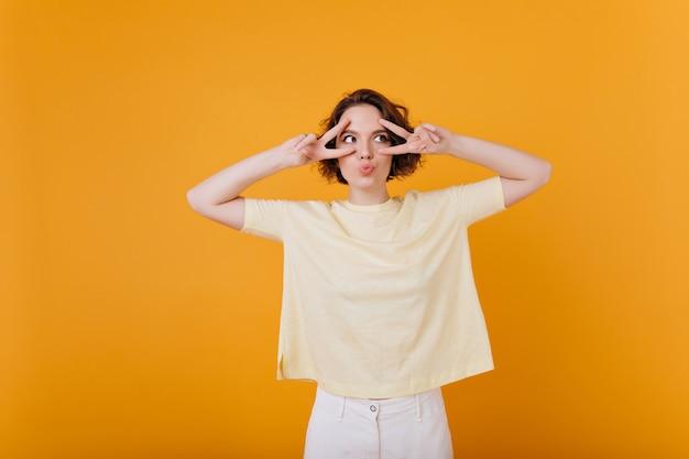 노란색 벽에 기쁨과 함께 포즈를 취하는 문신과 사랑스러운 귀여운 여자. 흰색 바지와 특대 티셔츠에 세련된 소녀의 실내 사진.