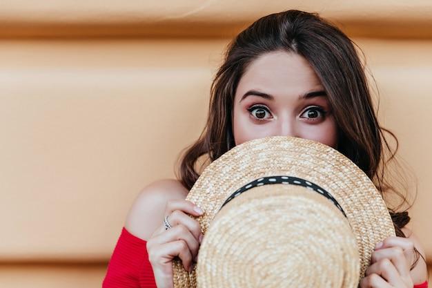 Adorabile ragazza dai capelli scuri in posa davanti al muro con l'espressione del viso sorpreso. colpo all'aperto di signora bruna di buon umore che si nasconde dietro il cappello estivo.