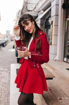Adorabile ragazza dai capelli scuri in gonna rossa che gode del servizio fotografico all'aperto