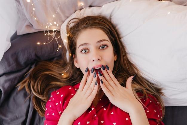 Adorabile ragazza dai capelli scuri con manicure nera sdraiata a letto ed esprimendo stupore. foto dall'alto della giovane donna spensierata dagli occhi azzurri in abito da notte rosso.