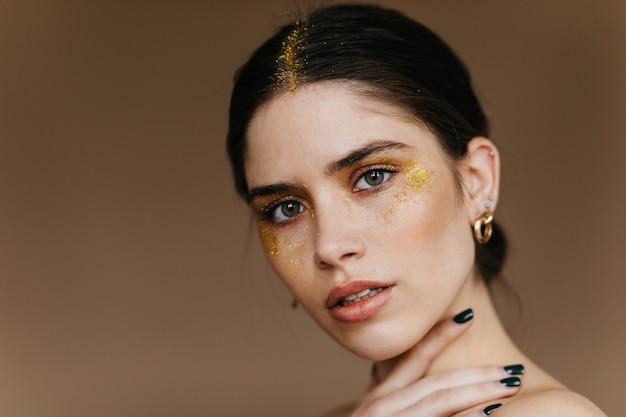 Adorabile ragazza europea con ombretti dorati. foto del primo piano della donna castana allegra isolata sulla parete marrone.