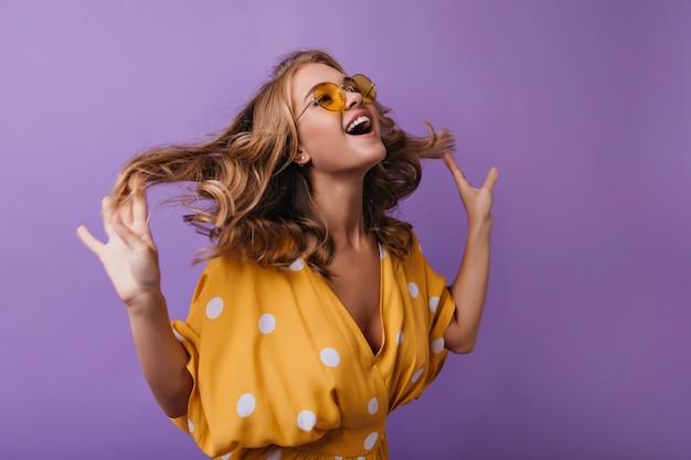 Очаровательная европейская женщина дурачится на фиолетовом. модная загорелая девушка играет со светлыми волнистыми волосами.