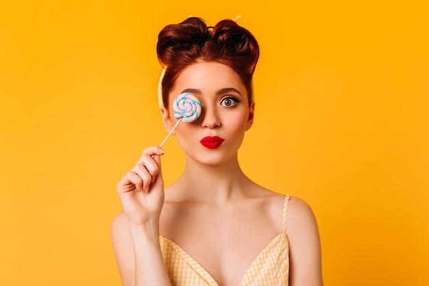ハードキャンディーを保持している愛らしい女性モデル。黄色の空間に分離されたロリポップとインスピレーションを得た生姜の女の子のスタジオショット。
