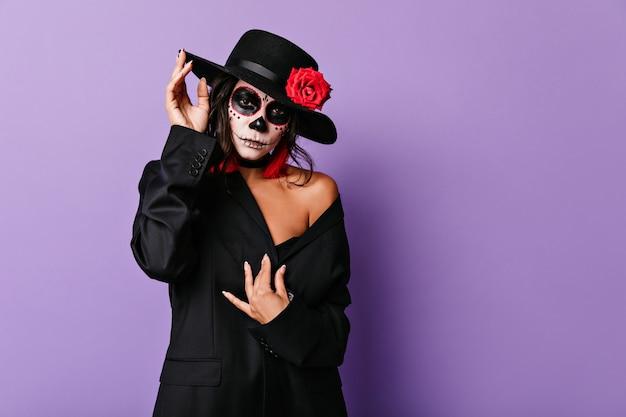 할로윈 사진 촬영을 위해 포즈를 취하는 검은 옷에 사랑스러운 여성 모델. 무서운 얼굴 그림으로 우아한 검은 머리 여자의 실내 초상화.