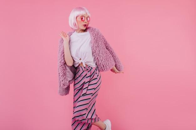 真面目な表情でポーズをとる流行の服を着た愛らしい女性モデル。ピンクの壁に隔離されたperukeの魅力的な白人の女の子の屋内写真