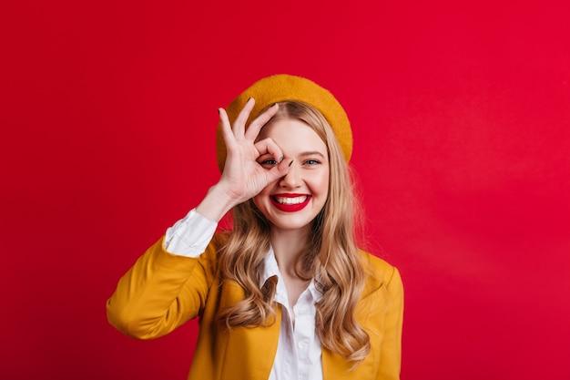 大丈夫な兆候を示している愛らしいフランスの女の子。赤い壁にポーズをとって陽気な笑う女性。