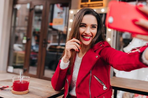赤い電話を持って自分撮りを作るかわいい笑顔の愛らしい女の子