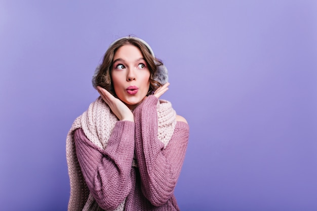 미소로 멀리 보이는 부드러운 니트 스카프로 사랑스러운 소녀. 따뜻한 보라색 스웨터에 아름 다운 여자의 근접 실내 초상화.