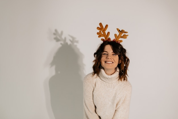 Lovable happy laughting woman with wavy short hair wearing white sweater in christmas headgear posing