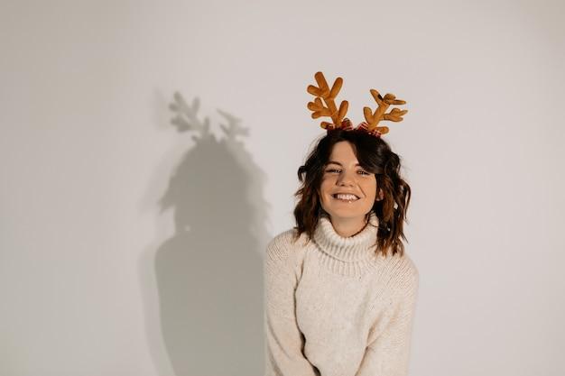 Симпатичная счастливая смеющаяся женщина с волнистыми короткими волосами в белом свитере в рождественском головном уборе позирует