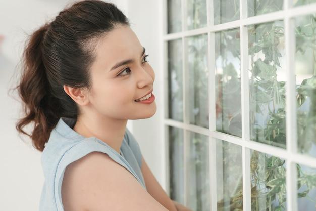 窓際に立って美しい庭を見ている愛らしい女性。