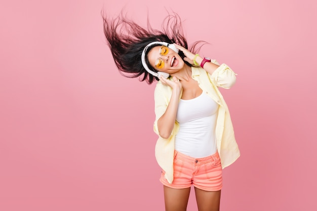 Lovable latin woman in white tank-top dancing with good music and waving hair. indoor portrait of graceful active asian girl in pink shorts relaxing in headphones.