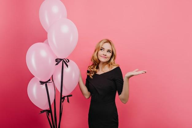 Amabile signora pallida in piedi vicino a palloncini con le mani in alto. ritratto dell'interno dell'affascinante ragazza di compleanno in attesa degli ospiti alla festa.