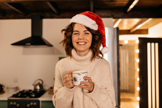 Lovable pretty woman with curly hair wearing knitted clothes and santa hat sitting on the kitchen and waiting for christmas party