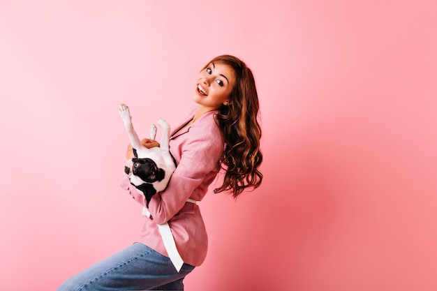 핑크에 프랑스 불독을 들고 사랑스러운 나가서는 소녀. 그녀의 강아지와 놀고 웃고 물결 모양의 헤어 스타일을 가진 영감을받은 아가씨.