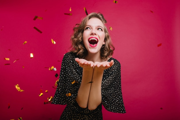 Lovable short-haired girl expressing positive emotions at party with confetti