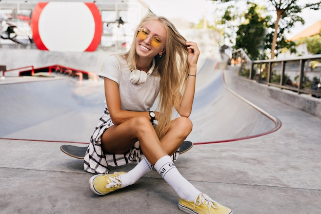Lovable skater woman playing with her blonde hair. outdoor portrait of gorgeous female model in yellow shoes sitting on skateboard.
